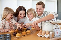 Loving family eating their muffins in the kitchen