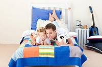 Cheerful father and his son watching a football match in the kid´s bedroom
