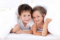 Happy Brother and sister playing on parent´s bed