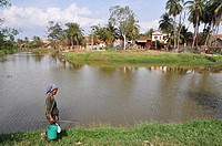 Siem Reap (Cambodia): a woman walking along the Siem Reap river´s bank