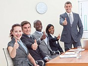 Businessteam with thumbs up after a presentation in office