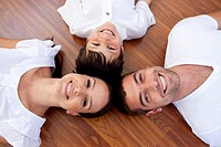 High angle of parents and kid lying on floor with heads together