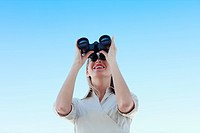 Young businesswoman looking through binoculars against blue sky