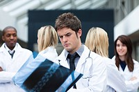 Serious doctor looking at an x_ray with his team in the background
