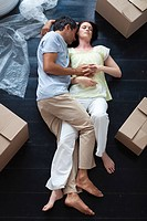 Lovers sleeping on the floor of their new house