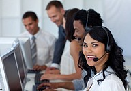 Smiling businesswoman in a call center with her multi_ethnic team