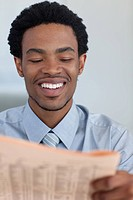 Smiling Afro_American businessman reading a newspaper in office