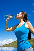 young woman drinks water from glass a bottle