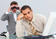 Angry businessman annoyed by a man looking through binoculars in the office