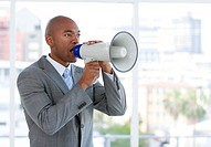 Ambitious businessman yelling through a megaphone in the office