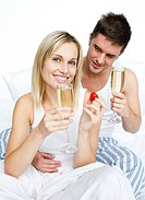 Couple eating strawberries and drinking champagne in bed