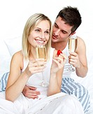 Young lovers eating strawberries and drinking champagne in bed