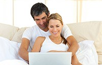 Enamoured couple using a laptop lying in the bed at home