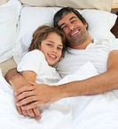 Loving father hugging his son lying in the bed