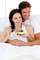 Joyful couple having breakfast lying in the bed