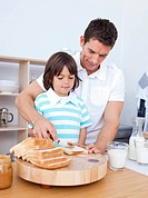 Charming father and his son spreading jam on bread in the kitchen