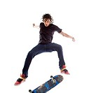 Rebellious, serious skateboarder doing stunt in mid_air on skateboard