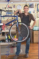 Business owner with broken bicycle on mounting bracket in workshop of bike shop