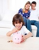 Joyful little boy inserting coin in a piggybank in the living room