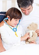Caring father and his sick son playing with a stethoscope sitting on a bed