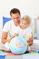 Attentive father and his daughter looking at a terretrial globe sitting on a bed