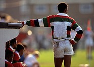 Rugby player on sidline watches the action on field