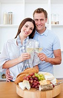Happy couple drinking white wine in the kitchen