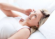 Smiling woman talking on phone lying on a bed at home