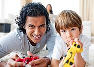 Happy father and his son playing video games lying on the floor in the living_room