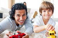 Cheerful father and his son playing video games lying on the floor in the living_room