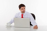 young business executive in white shirt behind desk with laptop