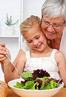 Happy grandmother cooking a salad with granddaughter in the kitchen