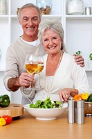 Happy senior couple eating a salad in the kitchen and drinkng wine