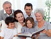 Family sitting on sofa reading a book in living_room