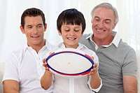 Son holding a rugby ball with his father and grandfather on sofa