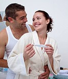 Happy young couple in bathroom holding a pregnancy test