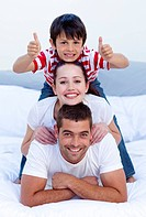 Happy parents and son playing in bed with thumbs up