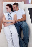Young couple lying together on sofa watching television