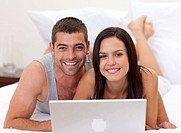 Smiling couple lying in bed using a laptop