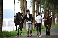 Young man and young woman walking side by side with two horses