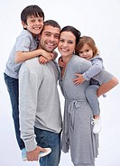 Happy parents giving children piggyback rides at home