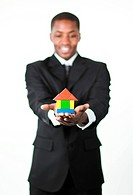 Young Friendly Afro_American businessman holding a house in his hands and looking at the camera