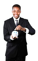 Smiling Afro_American businessman putting money in his piggy bank