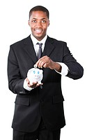 Friendly Afro_American businessman putting money in his piggy bank