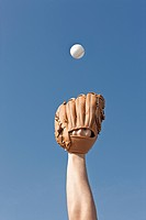 person holding baseball glove and ball