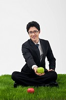 businessman sitting on grass holding apple