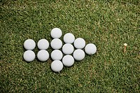 Arrow of golf balls in grass