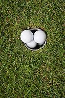 Golf ball falling into a hole