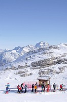 Skiers at ski lift in front of snow covered mountains, Gruppo della Marmolata, Dolomites, Italy, Europe