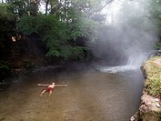 A man lies in the Kerosene Creek thermal hot spring near Rotorua in New Zealand